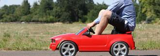 Man driving tiny red car
