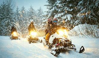 three snowmobiles driving through snow