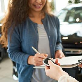 woman sign auto loan paperwork