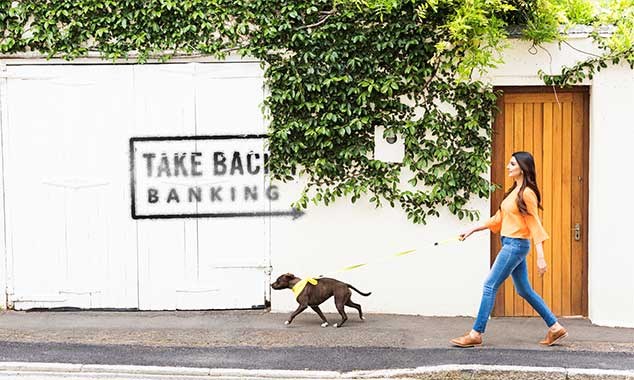 woman walking dog in from of Take Back Banking sign